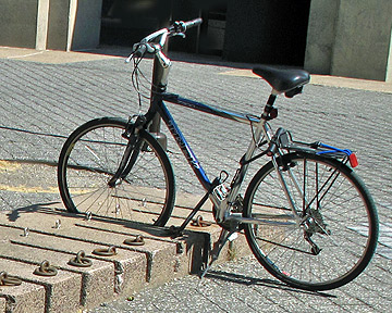 Here is a wheel-bender that I photographed at MIT a few years ago.  The main characteristic of a wheel bender is that it holds the bottom of the wheel without supporting the frame.  This maximizes the leverage for bending the wheel if the bike is knocked over.