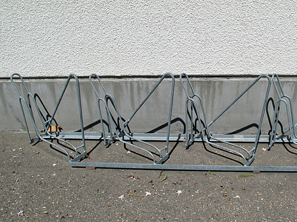 "In a couple of places, the ""low"" version of the bike parking is installed diagonally, where there is not sufficient space for the bikes to be perpendicular.  This view shows the locking loop beside the wheel-holder clearly."