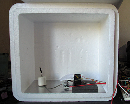 "Here is the interior of the styrofoam box, with the lid open.  The 6""×12"" aluminum plate covers the bottom.  The thermistor is on the left, propped up by a rubber foot, the resistor in is the center, and the fan is sitting on a foam pad on the right. (The foam is to reduce noise until I can get the fan proper mounted in a baffle.)"