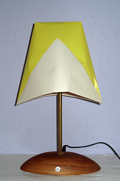 Here is the lamp, turned off.  The base is a wooden bowl from the thrift store, sanded so that it sits flat.  The upright is a standard brass lamp pipe, and the shade is just folded out of a 0.5m square of paper (the most common fold for making a paper cup).