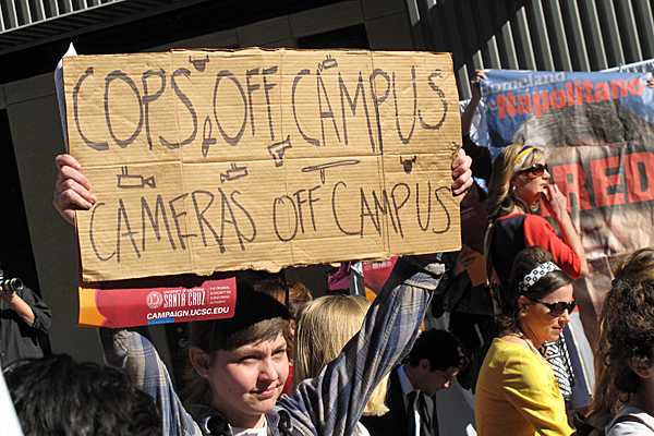 """One of the protestors with a cardboard sign saying """"COPS OFF CAMPUS   CAMERAS OFF CAMPUS"""" A larger banner calling for firing the President of UC can be seen on the stage in back."""