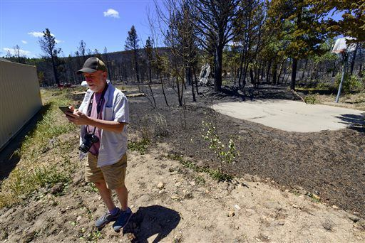Lester Karplus checks his cell phone after checking on his home and finding it unharmed by the Cold Springs Fire in Nederland, Colo., on Tuesday, July 12, 2016. The fire came within feet of his home. (Matthew Jonas/The Daily Camera via AP) [http://www.starherald.com/news/regional_statewide/colorado-wildfire-forces-evacuations-of-over-homes/article_ad0266d0-11a6-5c88-a397-2ae503cda789.html?mode=image]