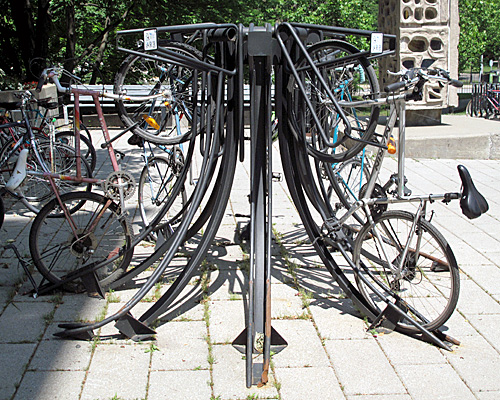 This 8-bike rack was spotted on the McGill college campus, in front of their natural history museum. It makes a nice sculptural statement, and is moderately compact, but looks a little difficult to use with tandems, recumbents, children's bikes, and others that don't fit the rather narrow idea of what the dimensions of an adult bike are.