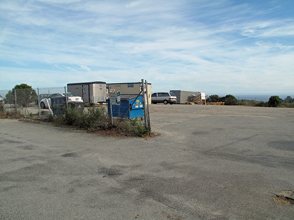 Another view of Lot 3, showing more random storage and trailers.