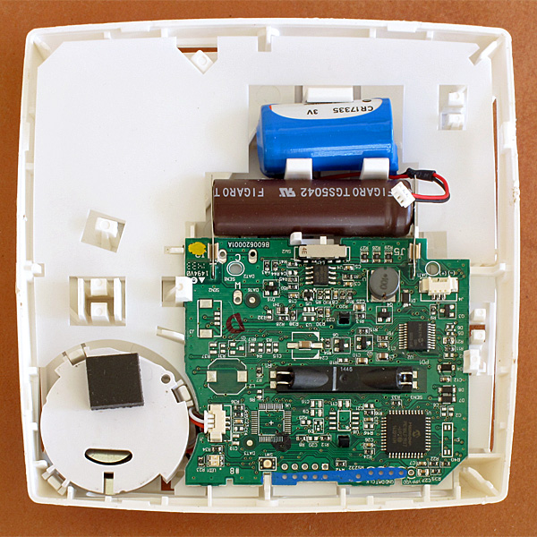 The wires from the blue battery have been disconnected from the white header on the PC board. The big brown cylinder is the CO detector, the white disk on the bottom left is the loudspeaker, and the black box in the middle is where the LED and photodetector are housed for the optical smoke detection.